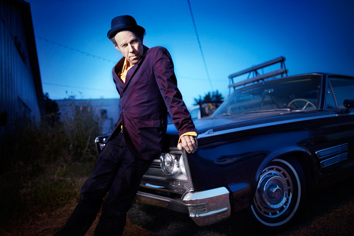 Tom Waits leans on a car
